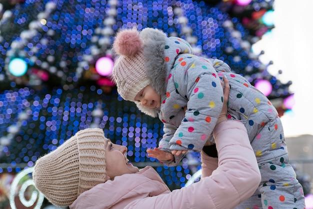 ママは通りのクリスマスツリーの背景に赤ちゃんを投げます。