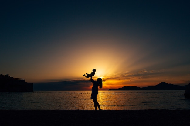 엄마는 그녀의 작은 아들을 던지고 일몰 해변에서 그와 함께 연주