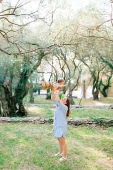 엄마가 아이를 던지고 올리브 과수원의 나무들 사이에서 그와 놀아요