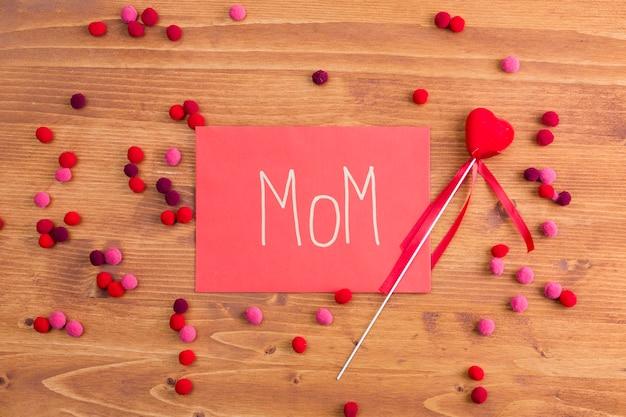 装飾的な心の近くのピンクの紙の上のママのタイトル