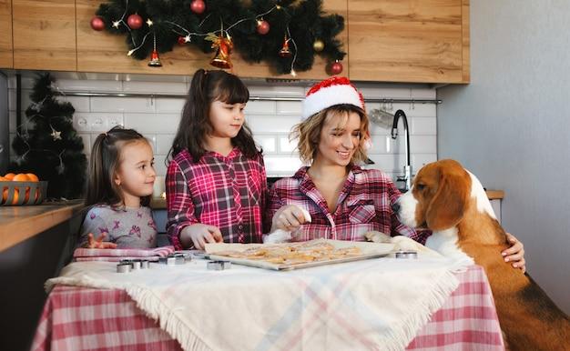 엄마는 딸들과 사랑하는 개와 함께 생강 쿠키를 준비하고 부엌에서 즐거운 시간을 보냅니다. 크리스마스 준비. 가족 전통.