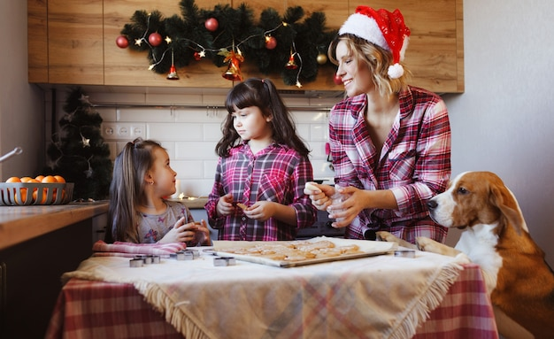 Mom together with her daughters and her beloved dog prepare ginger cookies and have fun in the kitchen. preparation for christmas. family tradition.