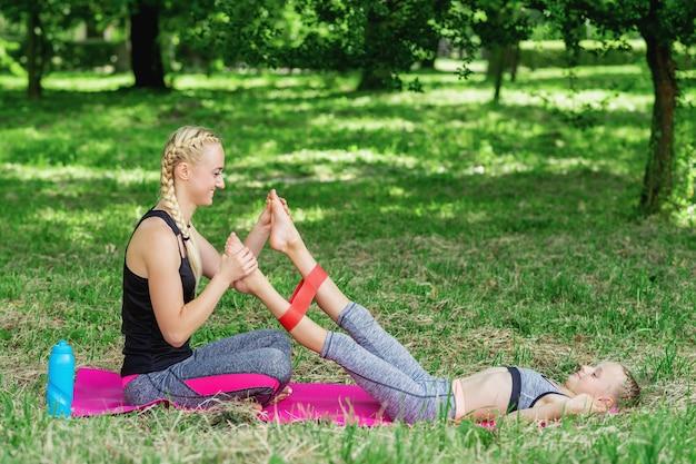 Мама тренирует ножки дочери с помощью жвачки для фитнеса