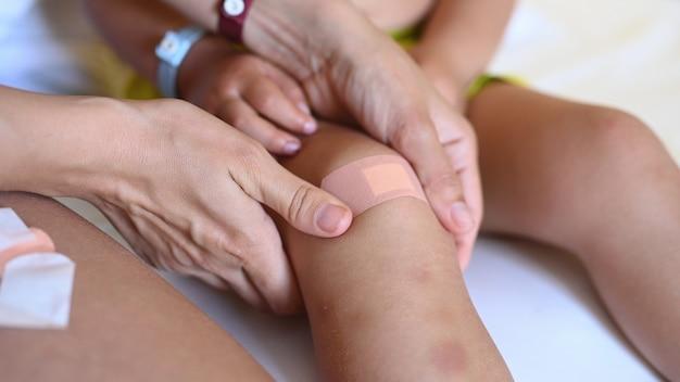 엄마는 아들의 부상당한 무릎을 치료합니다.