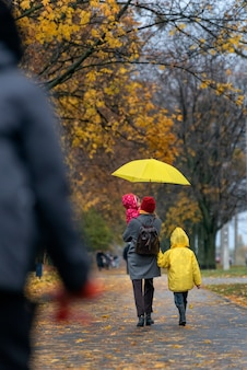 Mom and two children are walking in the rain along alley in the park on yellow trees background. vertical frame. back view.