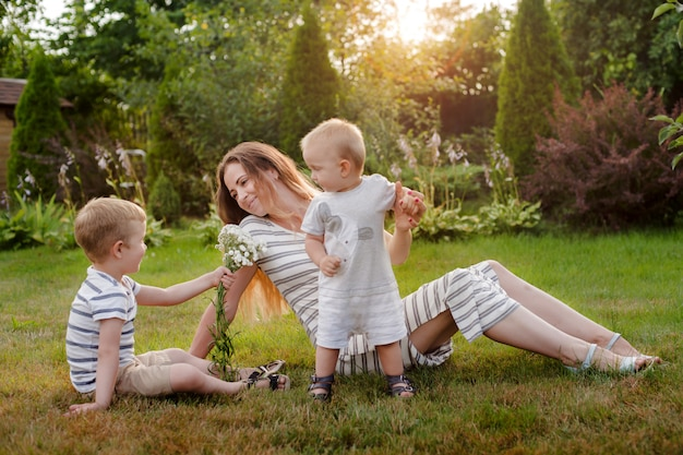 Мама, двое детей отдыхают на природе. соперничество между детьми. братья, материнство.