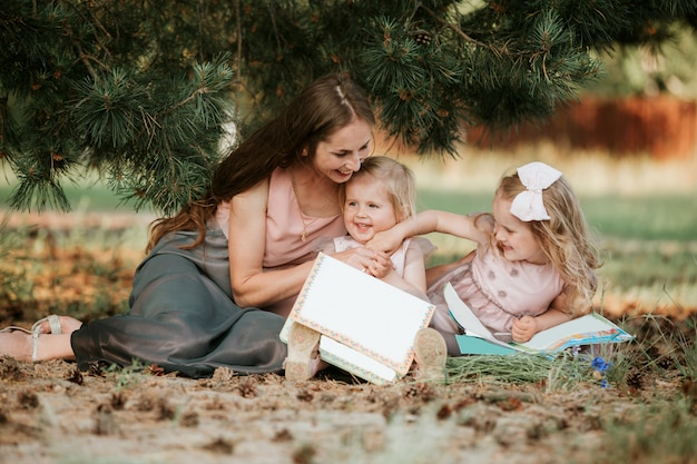 Mom and two daughters are sitting in a meadow and reading a book. happy family, mom and two daughters. mother's day concept