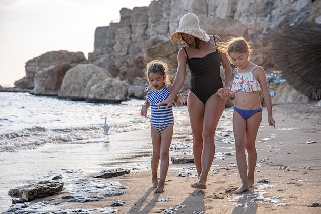 Mom and two little daughters walk along the seashore in swimsuits, looking at the sand. family vacation at the sea.