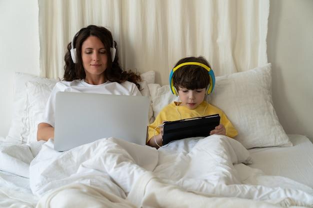 엄마는 취학 전 아들과 함께 침대에 누워 노트북 컴퓨터에 타이핑을 하고 태블릿으로 비디오나 만화를 봅니다.