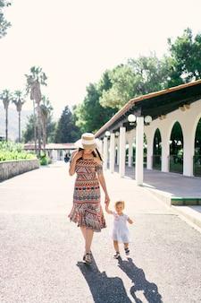 ママは公園の道に沿って小さな女の子の手を握って歩く