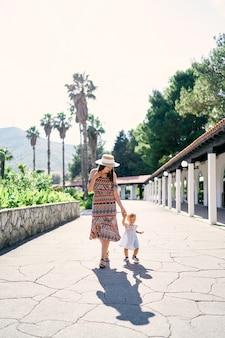 ママはヤシの木を背景に公園の舗装された小道に沿って小さな女の子と一緒に歩きます