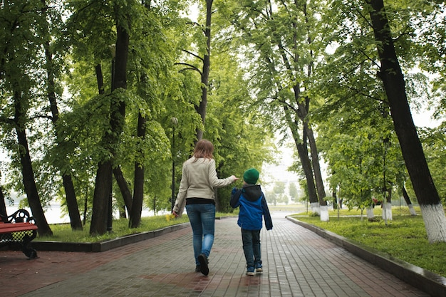 Mom walks with her son in summer, walks with family, family traditions, love and understanding