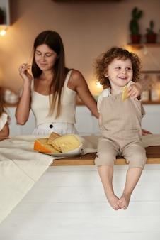 엄마는 아들이 테이블에 앉아 치즈를 먹는 것을 지켜 봅니다.