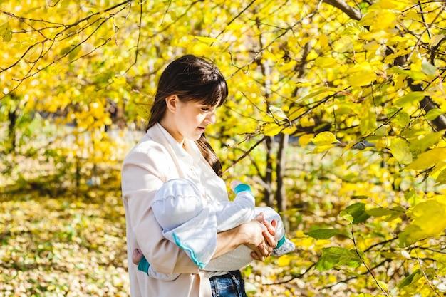 아기가있는 엄마, 작은 소년이 공원이나 숲에서 가을을 걷고 있습니다. 노란 잎, 자연의 아름다움. 자녀와 부모 간의 의사 소통.