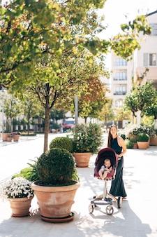 유모차에 아기를 태운 엄마는 녹색 덤불이 있는 욕조 근처 거리에 서 있다