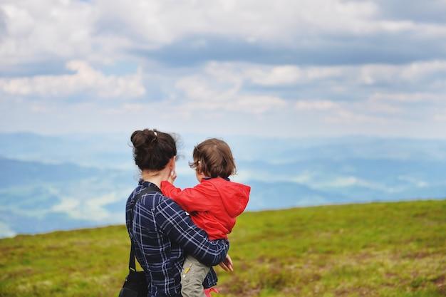 夏は山の頂上で赤ちゃんを抱いたお母さんが休んでいます。母親と赤ちゃんが山の頂上を見ています。
