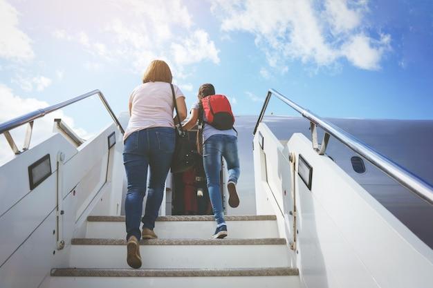 バッグを持ったお母さんと赤いバックパックを背負った娘が空港のフィールドにある飛行機のスロープに行きます。