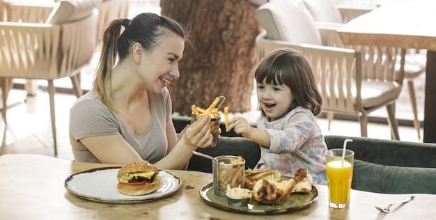 Мама с милой дочерью едят фаст-фуд в кафе