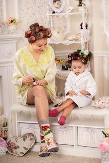 かわいい小さな娘とママは彼女の爪をペイントします。美しいお母さんと小さな娘の美しさの日。