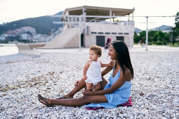 小さな女の子とお母さんは海沿いの小石のビーチに座っています