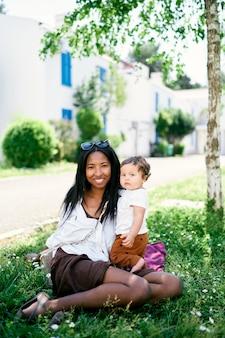 어린 소녀와 엄마는 녹색 잔디에 나무 아래 앉아