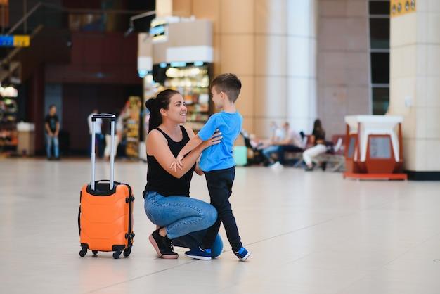 Мама с маленьким сыном и чемоданом в аэропорту. концепция путешествия
