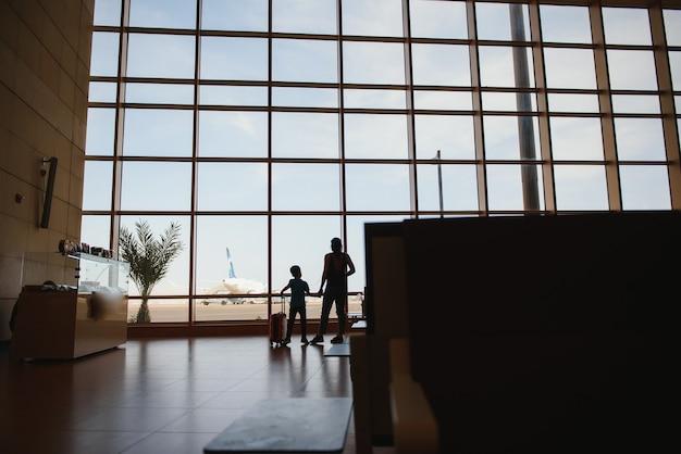 Мама с маленьким сыном и чемоданом в аэропорту.