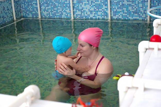 医療センターの特別な子供用プールで小さな赤ちゃんを持つお母さん。