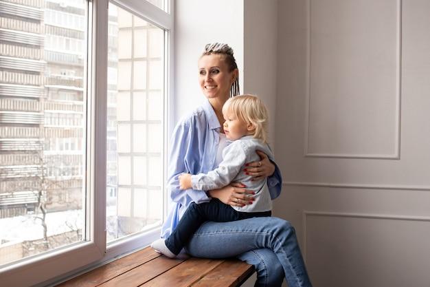 작은 아이를 가진 엄마는 창 밖을 내다 본다.