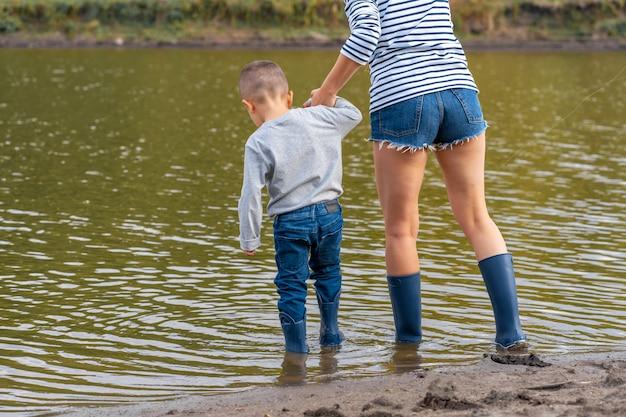 小さな息子とママはゴム長靴で湖の砂浜に沿って歩く