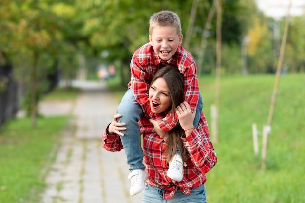 驚いた表情のママは、笑顔の息子を肩に抱えている。あらゆる目的のために。