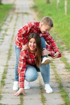 お母さんは、びっくりした表情でしゃがんで、笑っている息子を肩に抱えています。あらゆる目的のために。