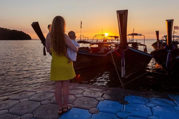 Мама с малышом наслаждается восходом солнца, стоя на пирсе pantone. вид сзади, сзади.