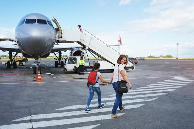 Mom with a bag and a daughter with a red backpack passengers go to the ramp of the plane on the airport field.