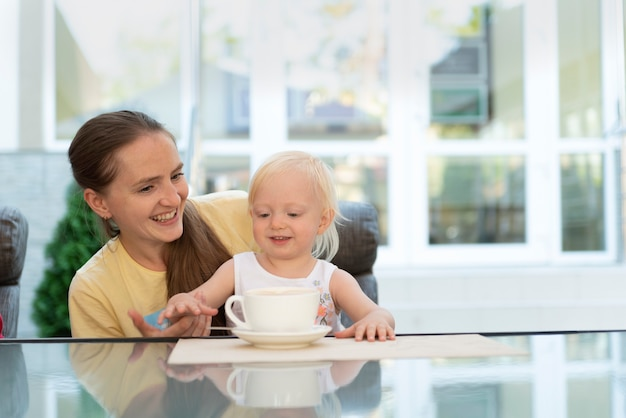 Mom with child in cafe drinks coffee. vacation with child.