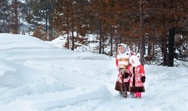 Мама с ребенком выходит из леса по сугробам. праздник день оленей северных народов ханты и манси.