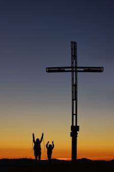 十字架の近くの山の頂上に子供を持つお母さんは勝利で腕を上げる