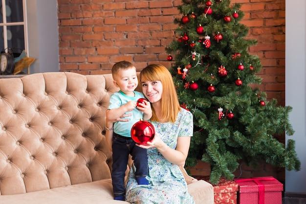 クリスマスの夜、冬の週末、居心地の良いシーンで遊ぶ子供とお母さん