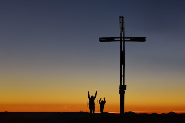 Mom with child on top of the mountain near the cross raise their arms in victory