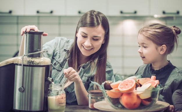 キッチンで子供を持つお母さんは新鮮なジュースを準備します