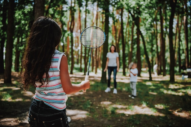 Mom with children playing badminton in sunny park