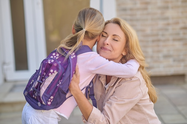 Mom with closed eyes hugging her daughter