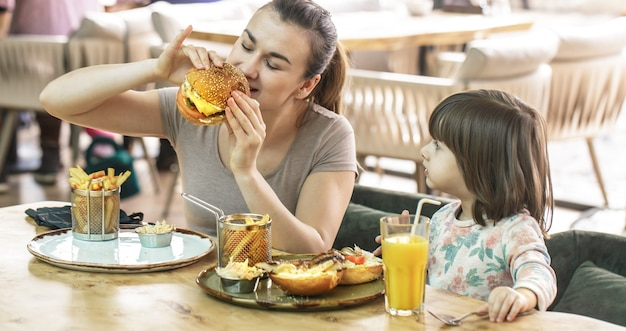 Mom with a cute daughter eating fast food in a cafe