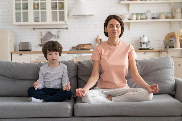 Мама с милым маленьким сыном, занимающимся йогой, сидят вместе на диване дома, учат ребенка медитировать