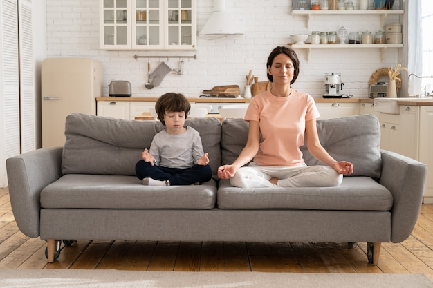 Mom with cute little son doing yoga exercise sit together on sofa at home teaching child to meditate