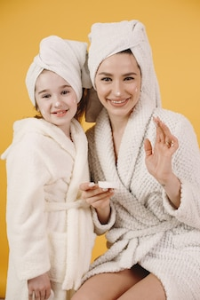 딸과 엄마. 흰 가운을 입은 소녀. 엄마는 딸에게 메이크업을 가르칩니다.