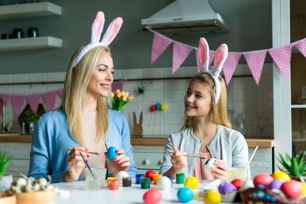 バニーの耳の娘とママは、キッチンでイースターエッグをペイントします。