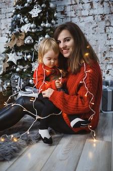 Мама с дочерью в красных теплых свитерах прыгают по кровати. счастливое материнство. теплые семейные отношения. рождественский и новогодний интерьер. любовь. семейное понятие.