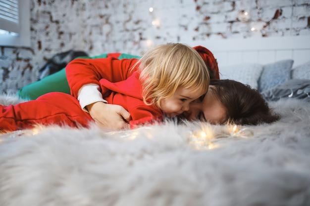 Мама с дочерью в красных теплых свитерах на кровати. счастливое материнство. теплые семейные отношения. рождественский и новогодний интерьер. любовь. семейное понятие.