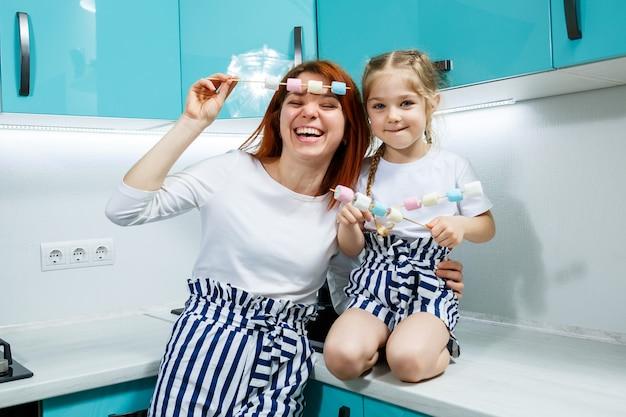 ターコイズブルーのキッチンで娘と一緒にママはマシュマロを食べます。素敵な家族関係。幸せな家族の概念、幸せな親と子